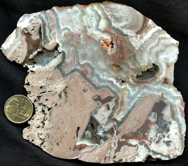 Figure 3. Specimen from a crustiform quartz breccia vein with slightly ferruginous chalcedony (pink) fragments and layers.